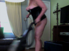 [Image: Vacuuming in a black leather corset and 6 inch black high heels]